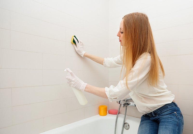 long-haired woman cleaning tile with sponge in bathroom